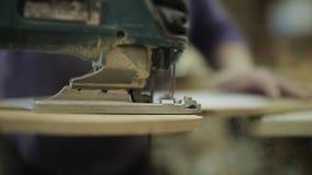 Close-up van elektrische figuurzaag in actie Vrouw met elektrische figuurzaag Scherpe Raad Voltooiing van segmenten productie stock video