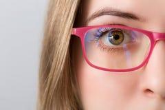Close-up van en oog van blondevrouw met roze glazen royalty-vrije stock afbeeldingen
