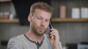 Close-up van ernstige, knappe mensen sprekende zaken wordt geschoten op de telefoon die stock video