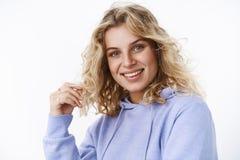 Close-up van flirty en vrouwelijke volwassen leuke vrouw in 25s met blauwe ogen wordt geschoten die met krul spelen en bij camera stock fotografie
