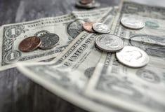 Close-up van gebruikte Amerikaanse die bankbiljetten en het munten op een houten bureau worden gezien Stock Foto's