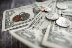 Close-up van gebruikte Amerikaanse die bankbiljetten en het munten op een houten bureau worden gezien Stock Afbeeldingen