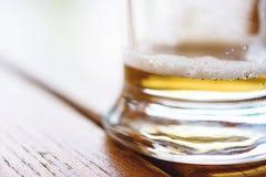 Close-up van gedeeltelijk Gebeëindigd Koud Glas Bier met Schuimend Schuim en Bellen op Ruwe Houten Lijst Royalty-vrije Stock Afbeelding