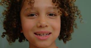 Close-up van gelukkig mengen-rasschoolmeisje die zich tegen bord in klaslokaal op school 4k bevinden stock videobeelden