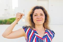 Close-up van gelukkige huiseigenaar of renter die sleutels tonen en u bekijken stock foto's