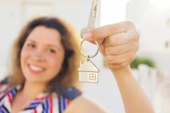 Close-up van gelukkige huiseigenaar of renter die sleutels tonen en u bekijken royalty-vrije stock foto's
