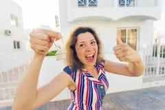 Close-up van gelukkige huiseigenaar of renter die sleutels tonen en u bekijken royalty-vrije stock foto