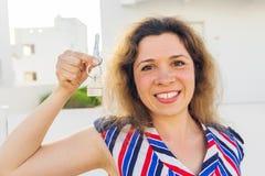 Close-up van gelukkige huiseigenaar of renter die sleutels tonen en u bekijken stock foto