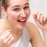 Close-up van gelukkige mooie jonge vrouw die een tandzijde houden stock foto