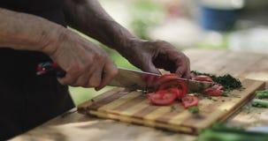 Close-up van gerimpelde handen van een oude vrouwen scherpe tomaten op een houten raad
