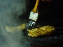 Close-up van geroosterde kip op B-B-Q Gebraden vlees en een olieborstel op een zwarte netachtergrond De ruimte van het exemplaar  Royalty-vrije Stock Fotografie