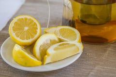 Close-up van gesneden citroenen dicht bij een theekop Royalty-vrije Stock Foto's