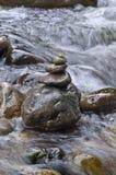 Close-up van gestapelde rotsen in stromend water stock afbeeldingen