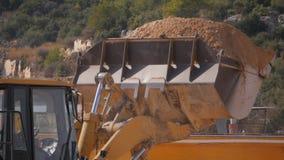 Close-up van geuploade emmer met steengrint tijdens de wegenbouwwerken stock afbeeldingen