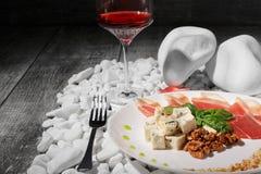 Close-up van gezonde snacks op een houten achtergrond Wijnglas, vork en plaat van ham, spinazie en kaas op witte rotsen Stock Afbeeldingen