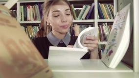 Close-up van glimlachende vrouwelijke student die geschikt kiezen van boekenkast stock videobeelden