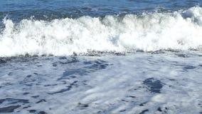 Close-up van golven die op de kust met overzees schuim breken Griekenland, eiland Santorini Perissastrand met zwart vulkanisch za stock videobeelden