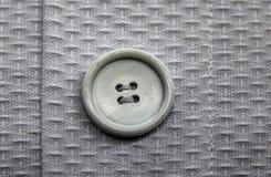 Close-up van greigeknoop op het lichtere kledingstuk van de keperstofstof met het stikken wordt genaaid die stock afbeeldingen