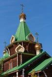 Close-up van groene daken en koepels van houten kerk op blauw s Stock Foto's