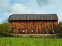Close-up van grote antieke ceder houten die schuur met steenstichting op groen gebied wordt gecentreerd Stock Foto