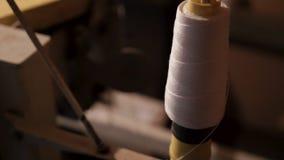 Close-up van grote spoel met witte draad voor verpakkingskorrel in zakken stock footage