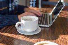 close-up van grote witte kop van latte en vrouw die laptop in bedelaars met behulp van Stock Afbeelding