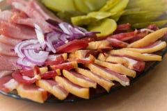 Close-up van ham, bacon, sla, komkommer en ui op papier, op een schotel royalty-vrije stock foto's