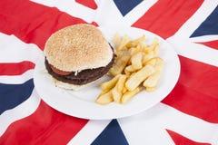 Close-up van hamburger en spaanders over Britse vlag Stock Foto's