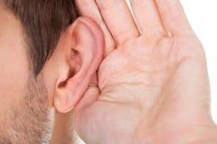Close-up van hand dichtbij oor stock afbeelding