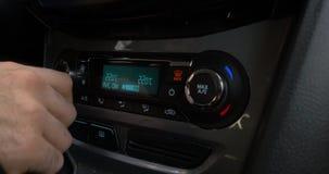 Close-up van hand die de airconditionerknoop in de auto aanpassen Mens die automobiel airconditioningssysteem met behulp van stock videobeelden