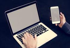 Close-up van hand die mobiele telefoon met computerlaptop achtergrond houden stock afbeelding