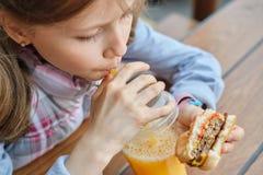 Close-up van hand van jong geitje dat hamburger eet en jus d'orange drinkt royalty-vrije stock afbeeldingen