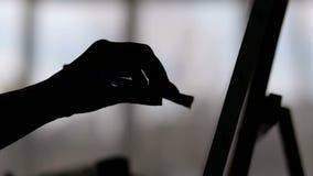 Close-up van hand van kunstenaar met een borstel, silhouet stock footage