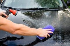 Close-up van Hand met purpere Borstel die zwarte Auto wassen De wasconcept van de auto mens die eigen auto met spons en zeep wass stock fotografie