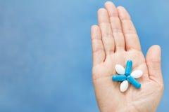 Close-up van hand wordt geschoten die blauwe en witte pillen in de vorm l houden dat Royalty-vrije Stock Foto