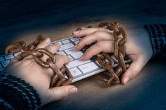 Close-up van handen, computertoetsenbord en oude roestige kettingen op donkere houten achtergrond Stock Foto