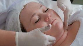 Close-up van handen van de schoonheidsspecialist in witte handschoenen tijdens de procedure in het de kosmetiekcentrum Gezichtsma stock video