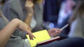 Close-up van Handen die pennen houden en nota's maken op de conferentie stock footage