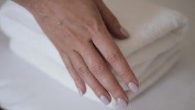 Close-up van handen die stapel verse witte badhanddoeken op het bedblad zetten Bediening op de kamermeisje het schoonmaken de mac stock videobeelden