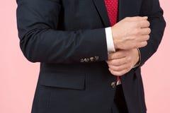 Close-up van handen die witte koker in blauw kostuum aanpassen stock foto