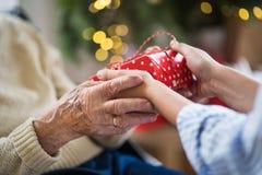 Close-up van handen van hogere en jonge vrouw die een heden houden bij Kerstmis royalty-vrije stock fotografie