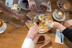 Close-up van handen met desserts en koffiekoppen in een koffie stock foto's
