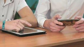 Close-up van handen van twee mensen die gadgets houden stock video