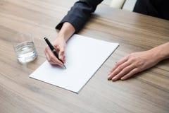 Close-up van handen van een de bedrijfsvrouw terwijl het neerschrijven van wat essentiële informatie Een glas van water, document Stock Fotografie