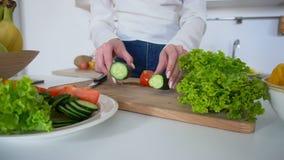 Close-up van handen van mooie vrouw wordt geschoten die gezonde lunch van groenten op scherpe raad in lichte keuken die voorberei stock footage
