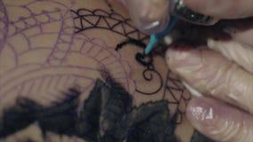 Close-up van handen van tatoegeringskunstenaar in handschoenen die een patroon op lichaamsmacro tatoeëren stock video