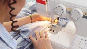 Close-up van handnaaisters die aan een nieuwe orde werken die een naaimachine met behulp van stock videobeelden