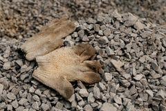 Close-up van handschoen en grint zwarte rots op bouwwerf voor achtergrond wordt geschoten die De bouw is het proces om een bui te royalty-vrije stock foto