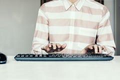 Close-up van handvrouw gebruikend een muis en typend op toetsenbord op witte lijst, bedrijfsconcept stock afbeelding
