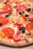 Close-up van heerlijke Italiaanse pizza met ham, tomaten wordt geschoten die en Stock Afbeelding